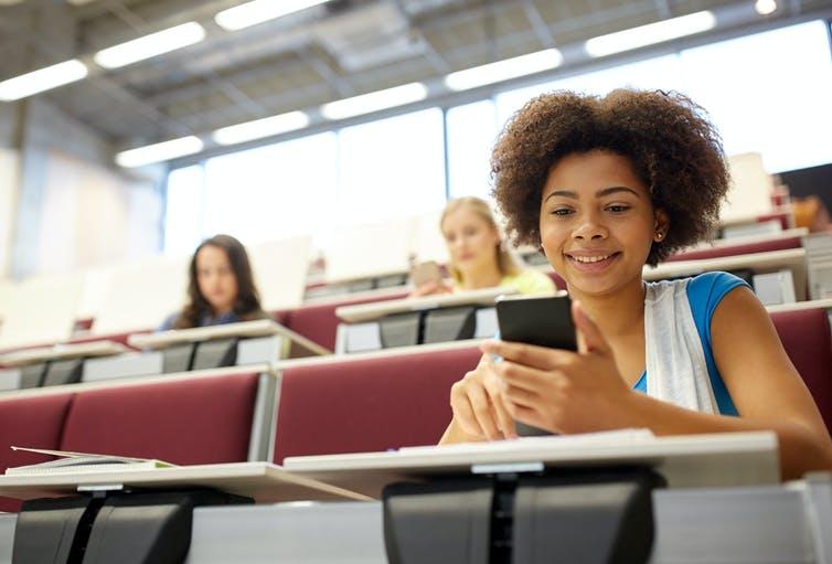 Une jeune fille consulte son téléphone cellulaire dans une salle de classe